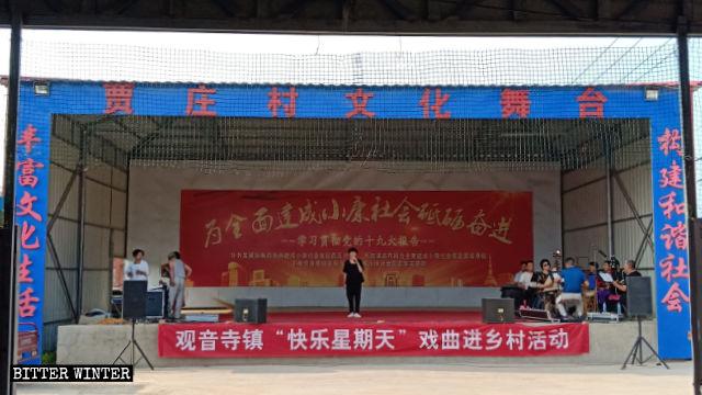 """贾庄村文化戏台正在演出,戏台上挂着""""快乐星期天""""的横幅"""