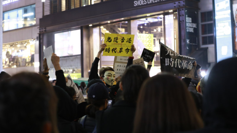 """一名示威者在人群中高举标语牌:""""光复香港时代革命"""""""